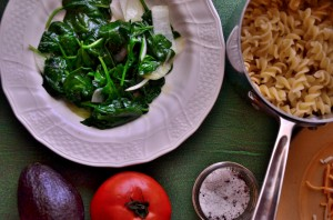Spinach on a plate and noodles in a sauce pan