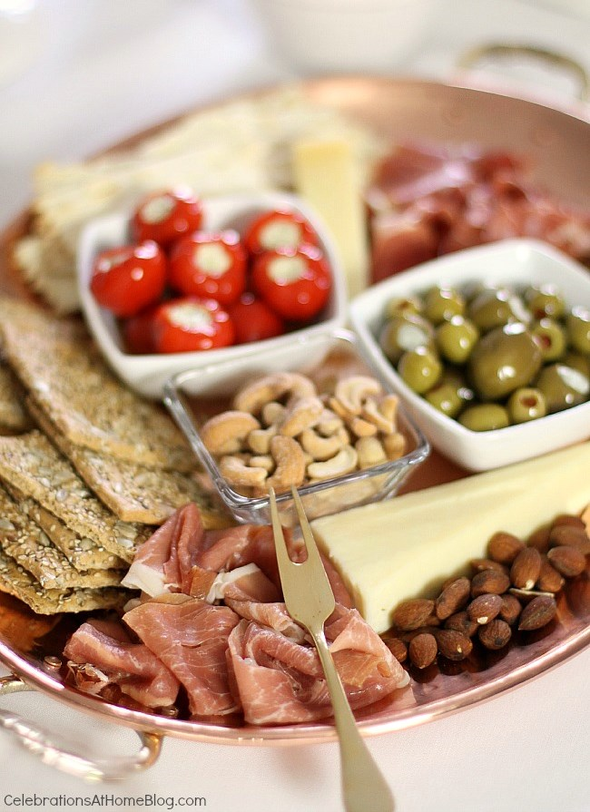 Small charcuterie board with prosciutto, olives, nuts, and crackers.