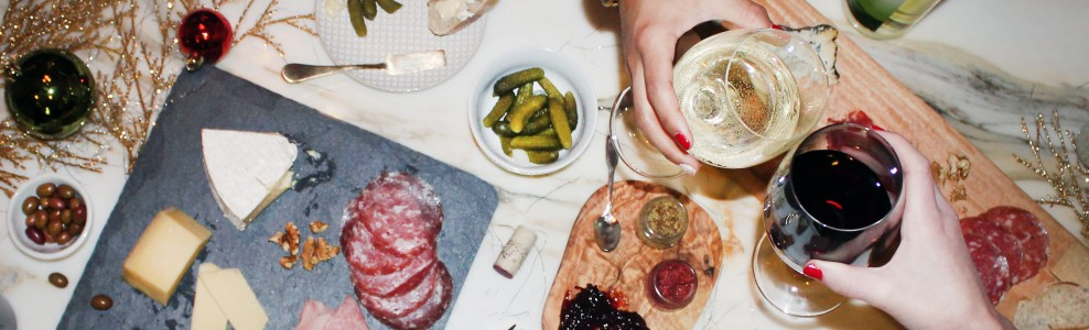 Toasting wine over a charcuterie board.