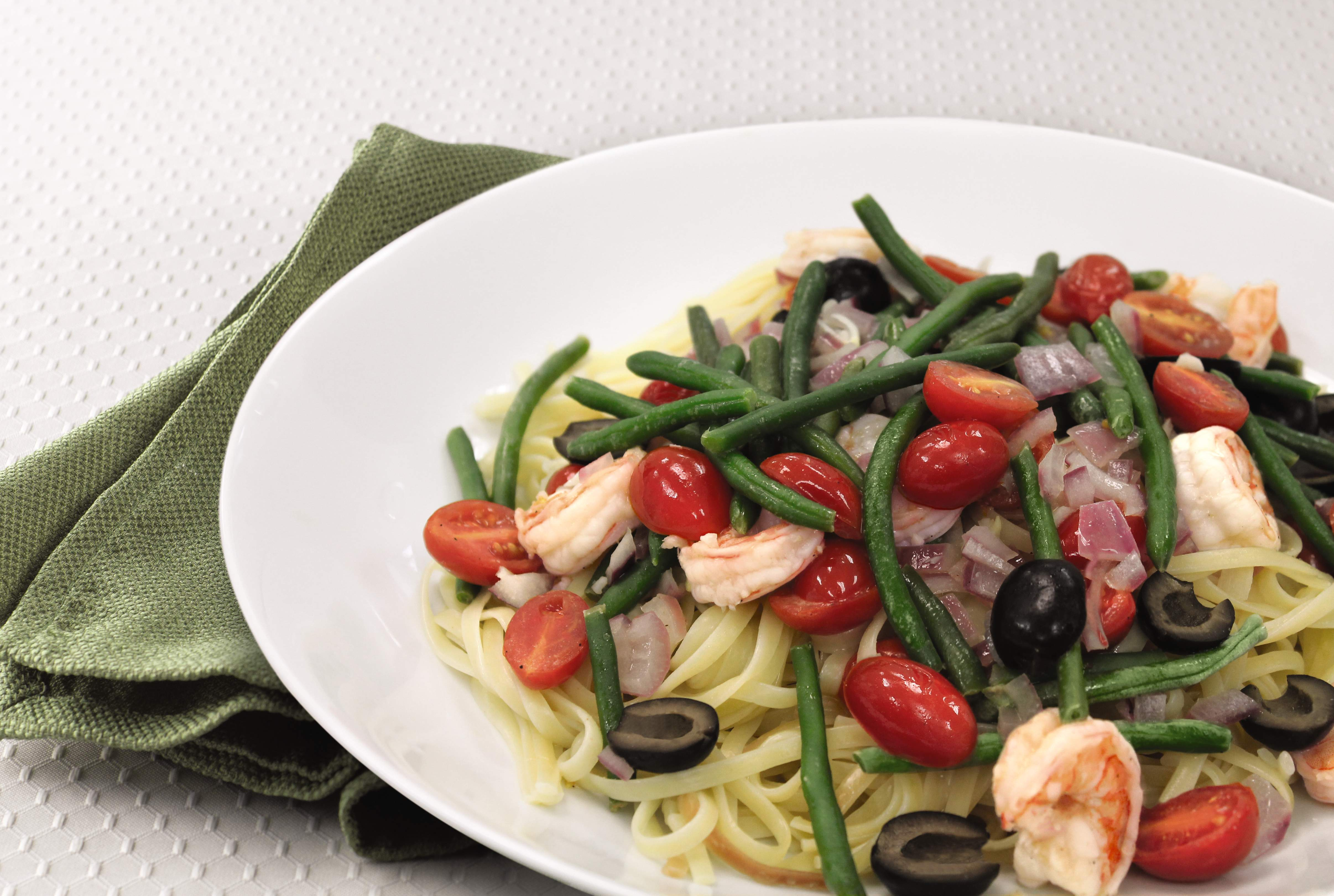 Shrimp nicoise pasta with tomatoes, black olives, and green beans.