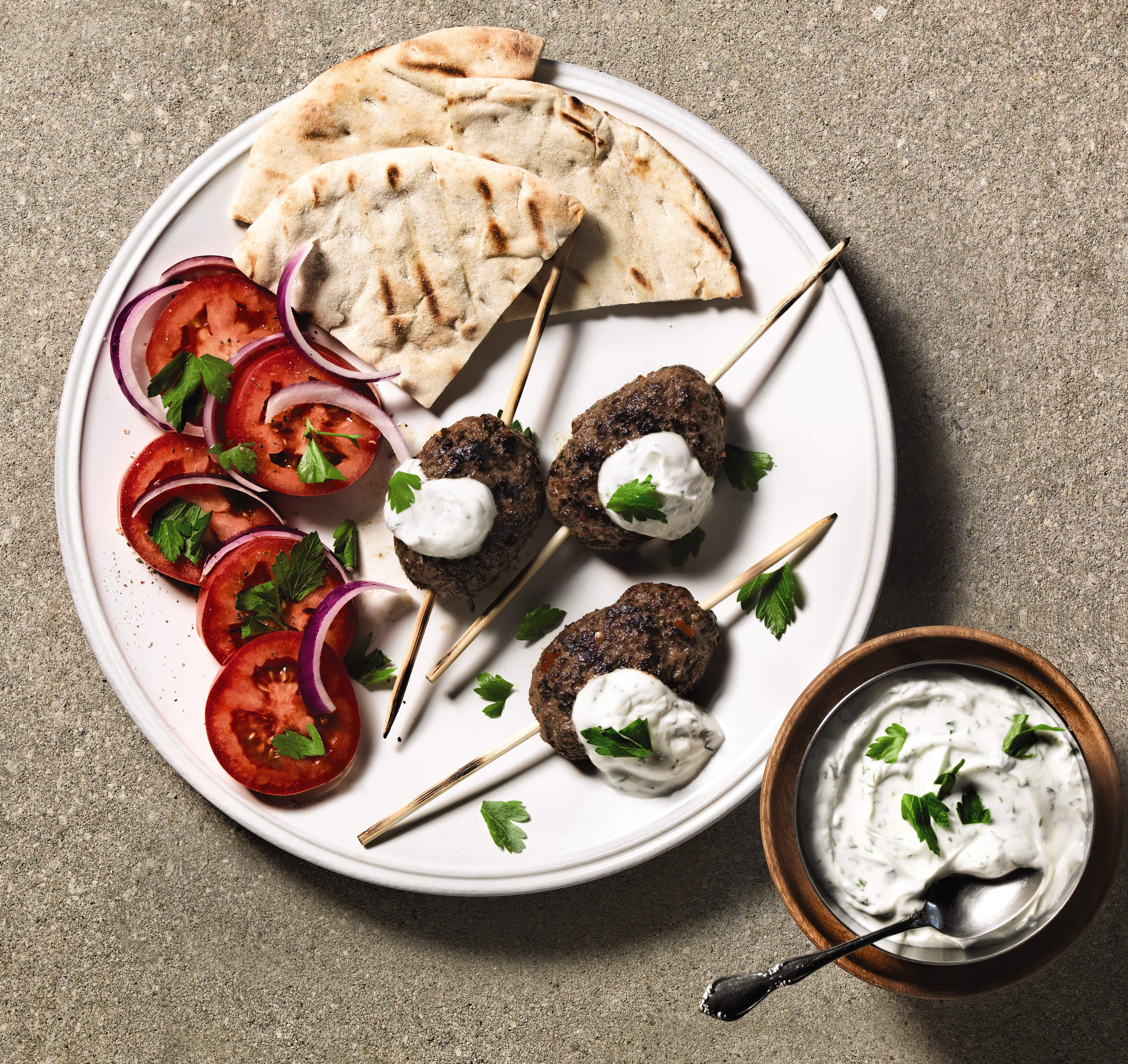 Beef skewers with tzatziki sauce and fresh tomato and onions.