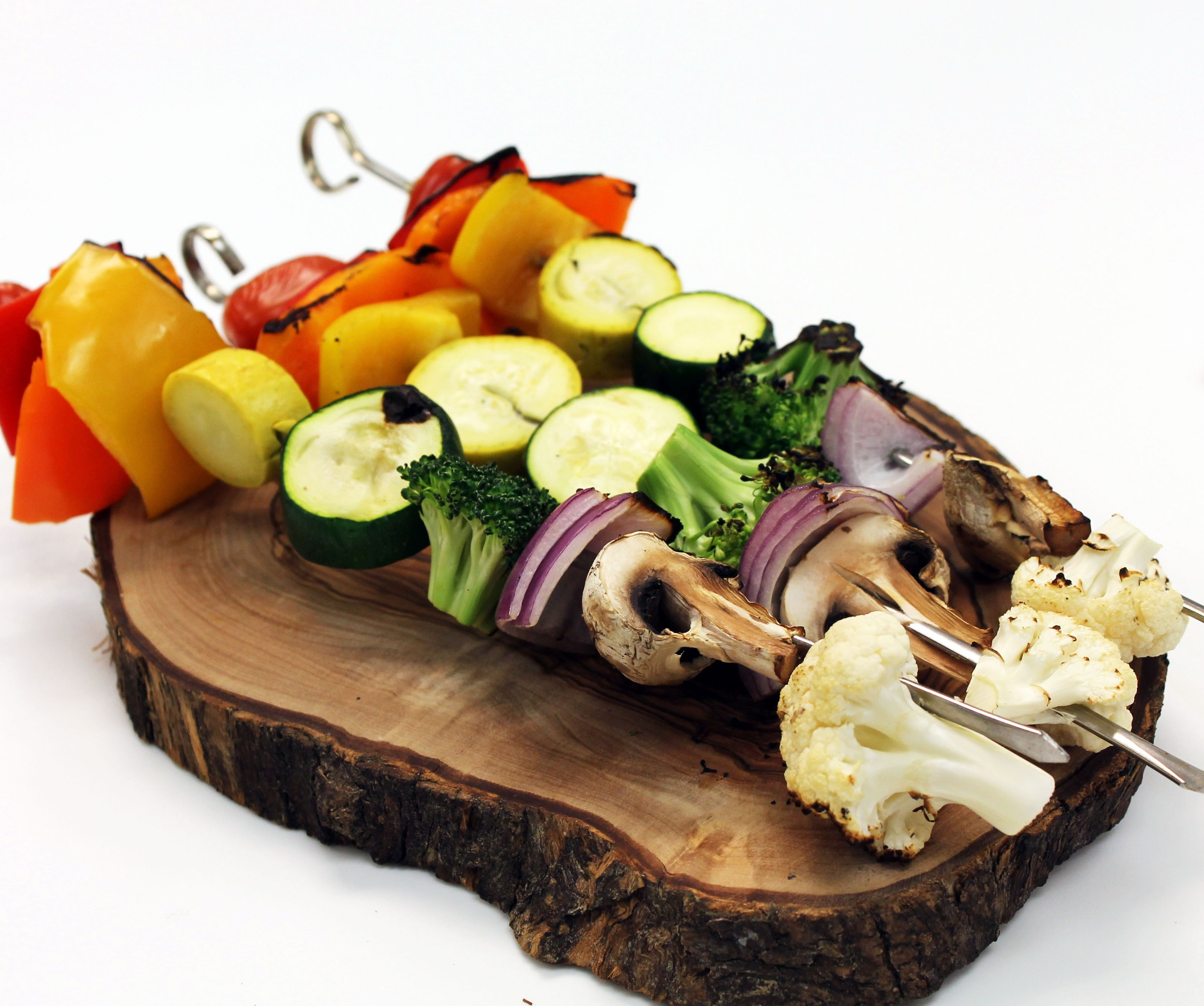 Grilled vegetable skewers on a decorative wooded plate.
