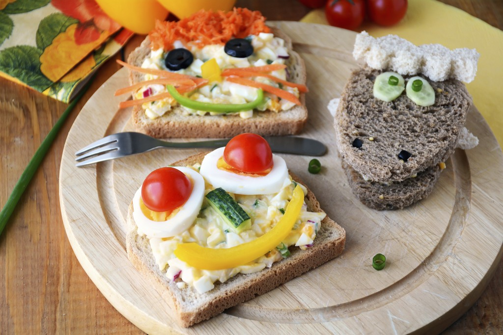Three fun lunch sandwiches with faces on them made from vegetables.