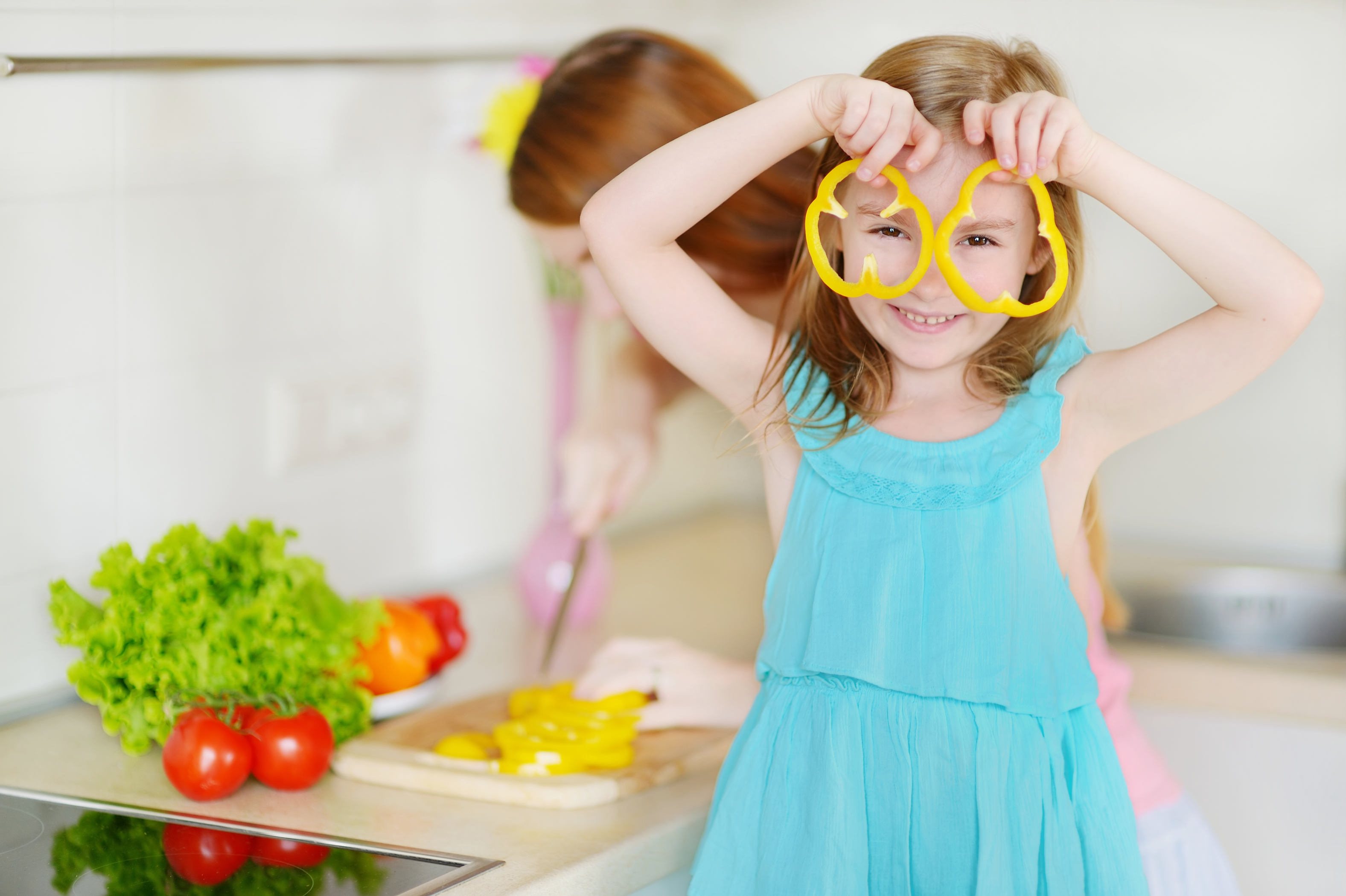 Small girl pretending sliced peppers are glasses while mom cuts more in background.