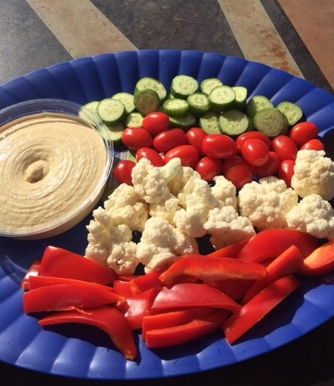 Hummus with red peppers, cauliflower, cherry tomatoes, and cucumber for dipping.