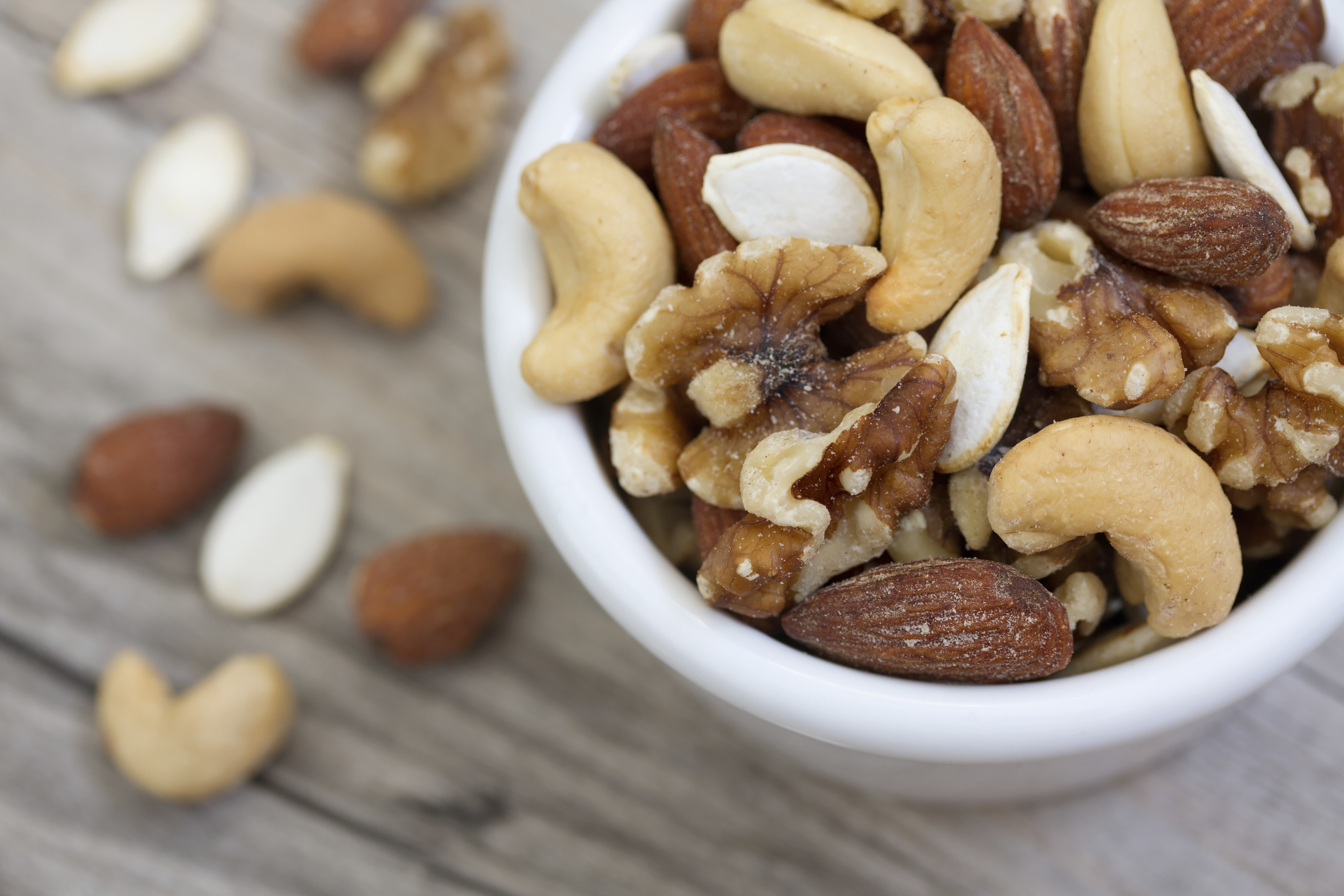 Mixed nuts in a bowl on a wooden tabletop.