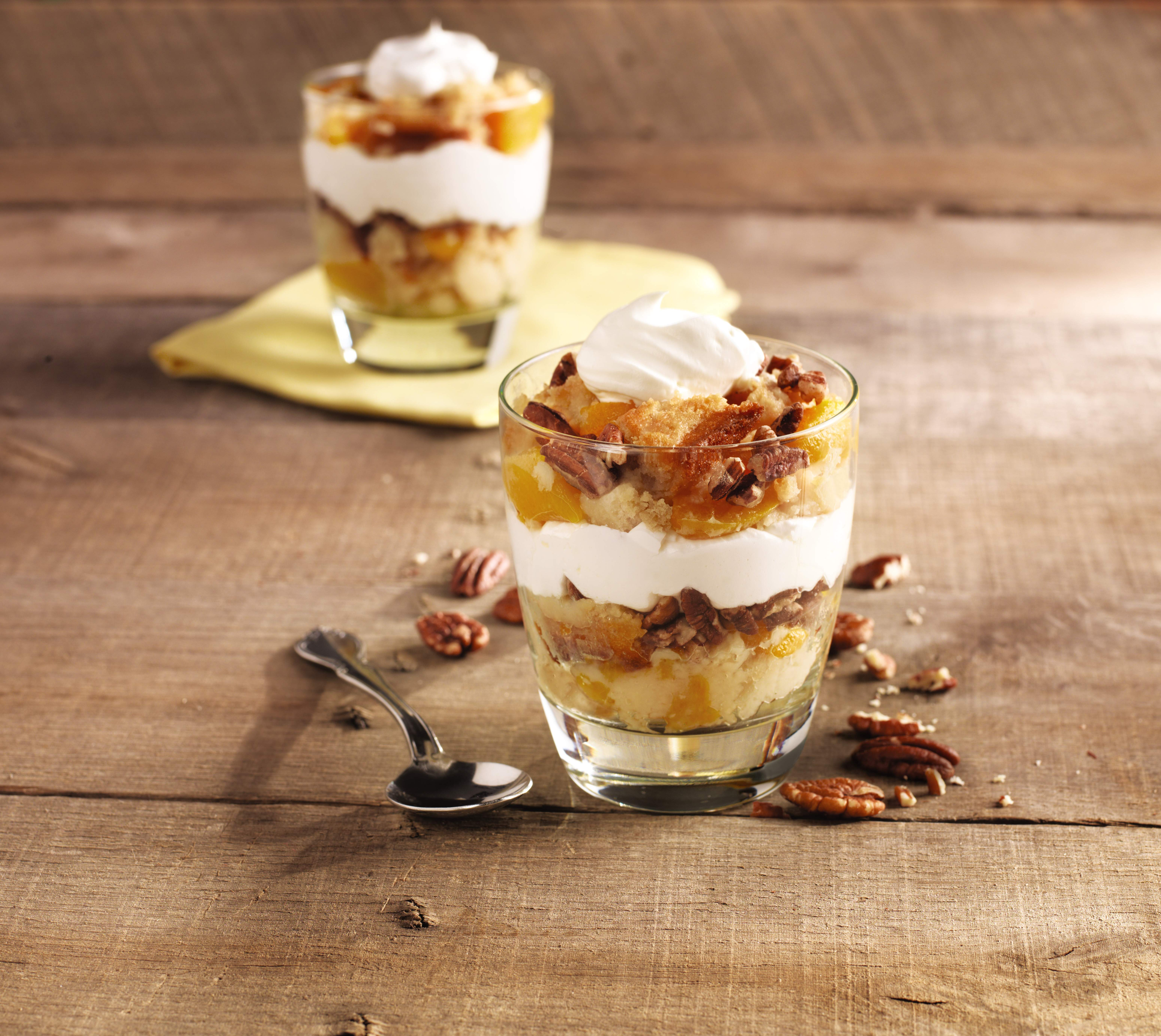Peach cobbler parfait with nuts and whipped cream.