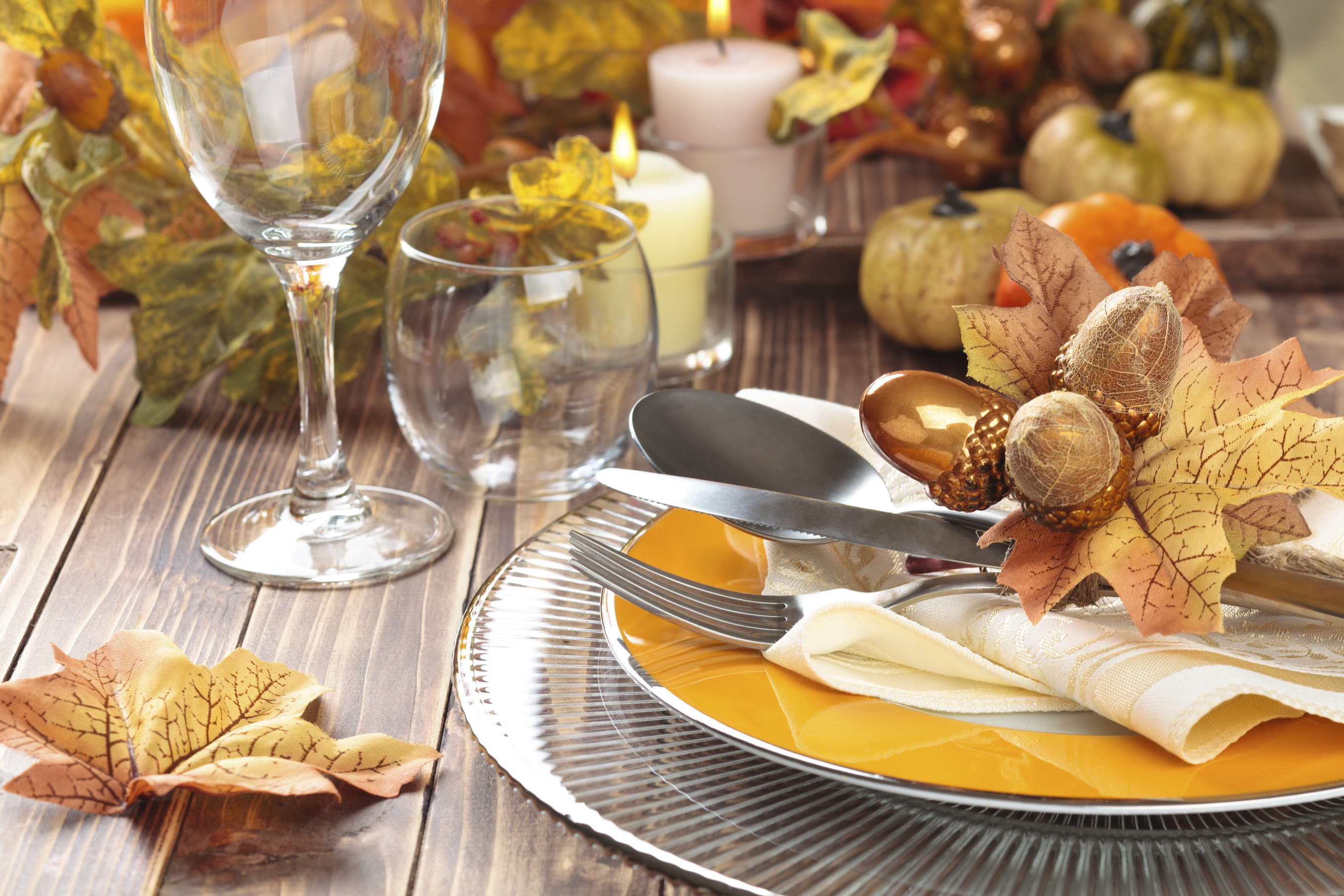 Autumn place setting with leaves, candles, and pumpkin.