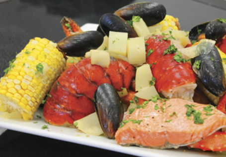 Seafood boil with lobster, mussels, salmon, potatoes and corn.