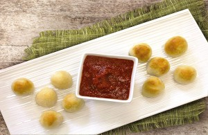 Cheesy Garlic Bread Poppers on a serving plate with dipping sauce.