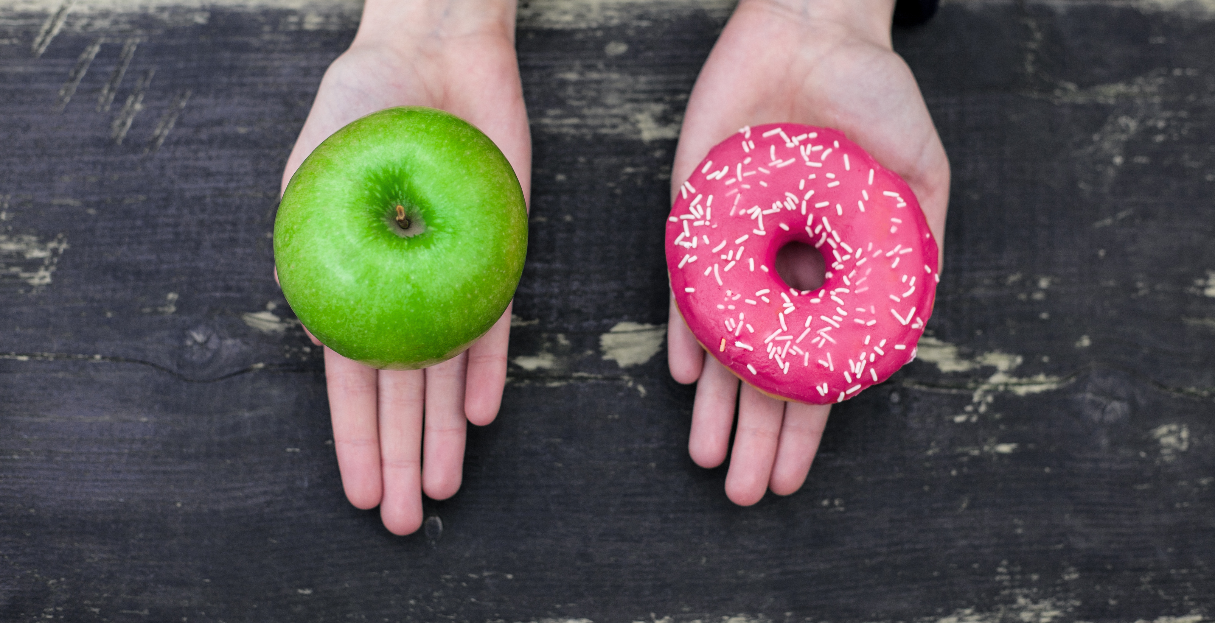Two hands open holding an apple in one and a donut in the other.