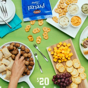 A spread of ALDI finger foods for $20 and under including Pepperoni Pizza Snacks, Pretzel Slims, Crackers and red grapes.