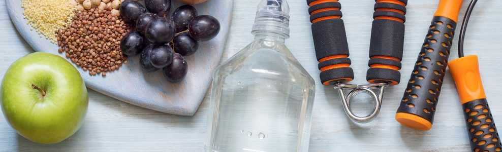 Fitness tools including a jump rope next to a bottle of water and fresh grapes.
