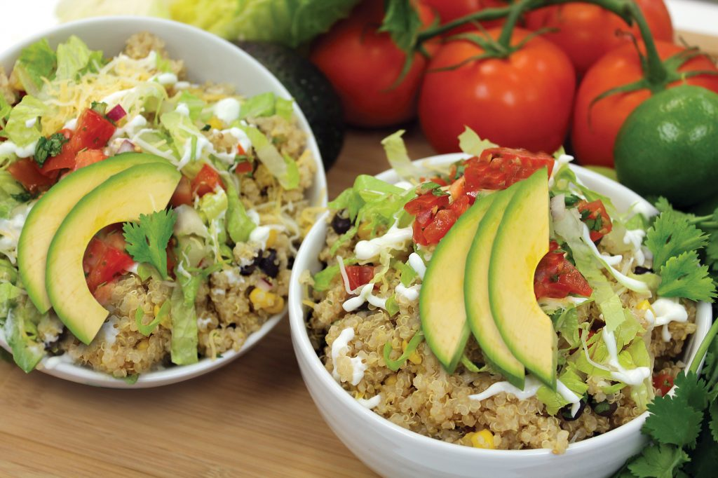 Quinoa burrito bowl topped with fresh avocado and tomatoes.