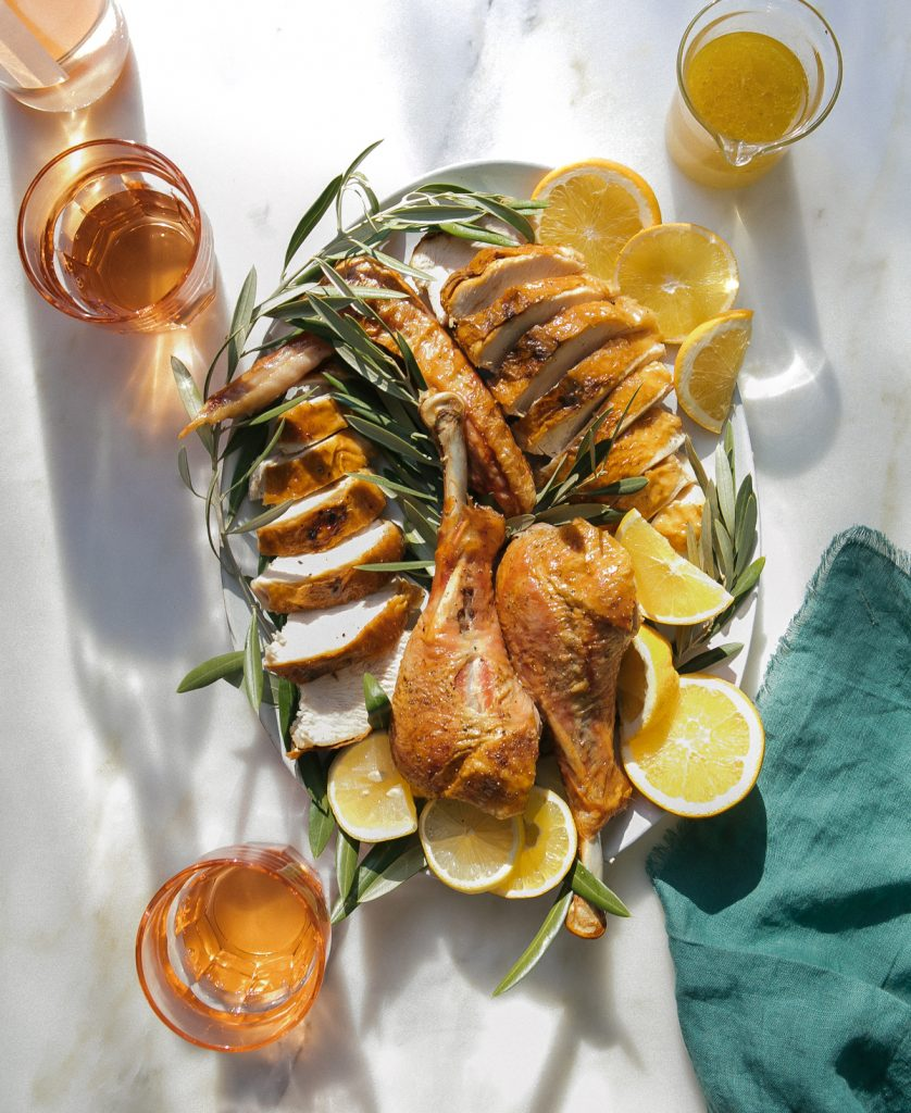 Mojo sheet pan turkey on a serving platter garnished with oranges and olive branches.