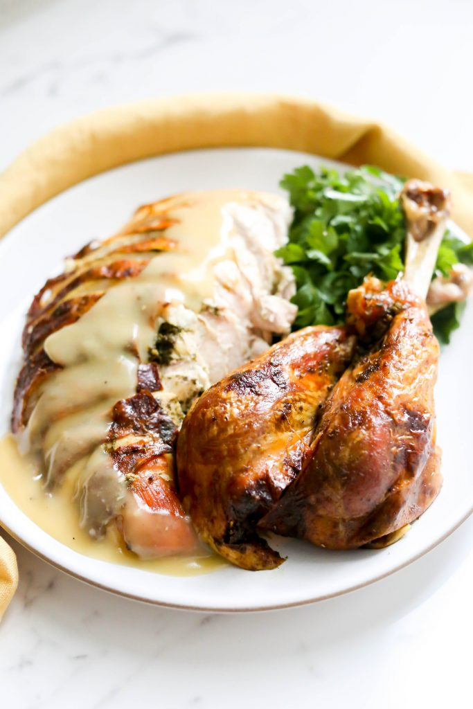Herb-Brined Turkey topped with Garlic Pan Gravy on a plate.