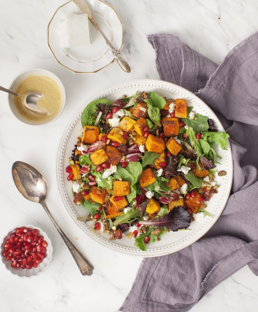 A plate full of Spiced-Up Fall Squash Salad with extra pomegranates and Cider Date Dressing on the side.