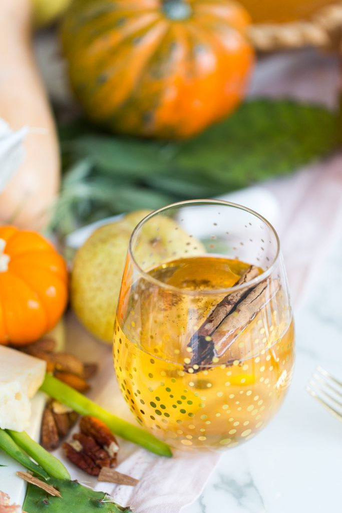 A stemless wine glass filled with Sparkling Pumpkin Cider and garnished with a cinnamon stick.