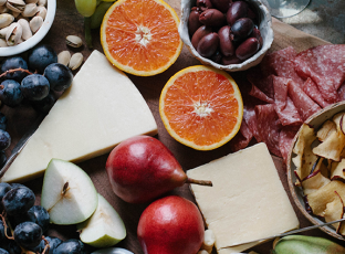 A lush cheese & charcuterie board with oranges, pistachios, salami and more.