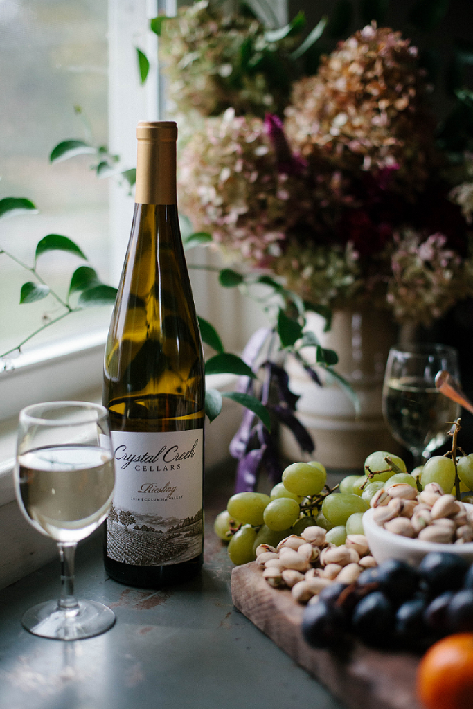A bottle of Crystal Creek Cellars Riesling next to a charcuterie board filled with pistachios, olives and grapes.