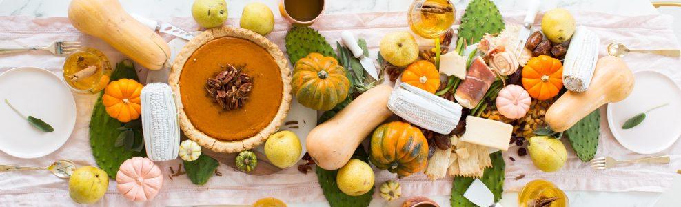 A Friendsgiving table setting with squash, pumpkin and sparkling pumpkin cider.