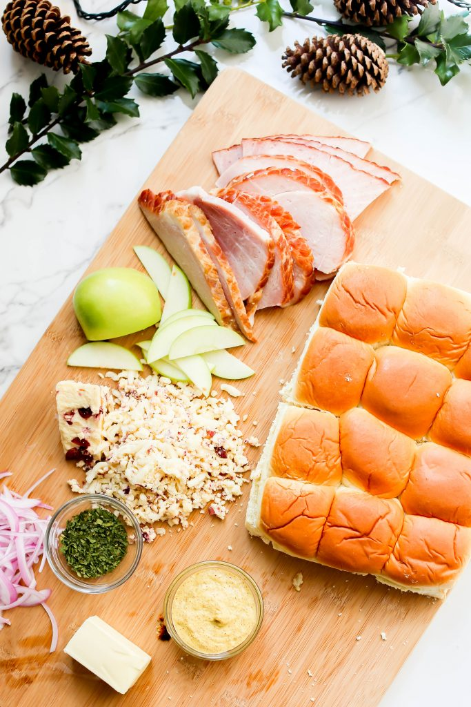 All the ingredients you need for holiday ham sliders on a cutting board.