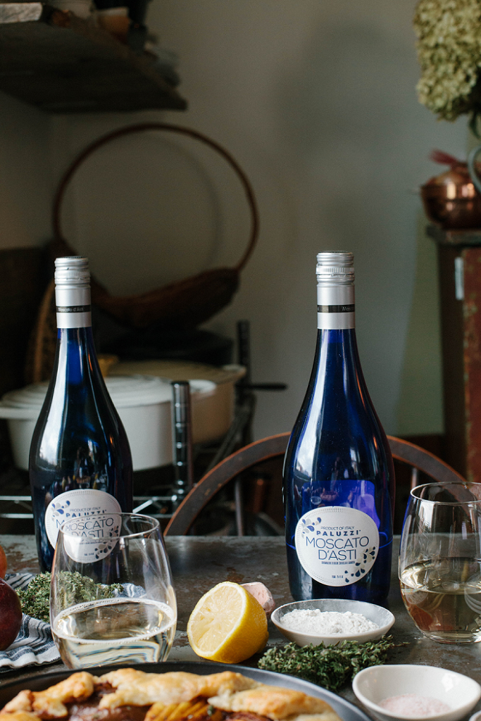 Two bottles of Paluzzi Moscato on a dining table.