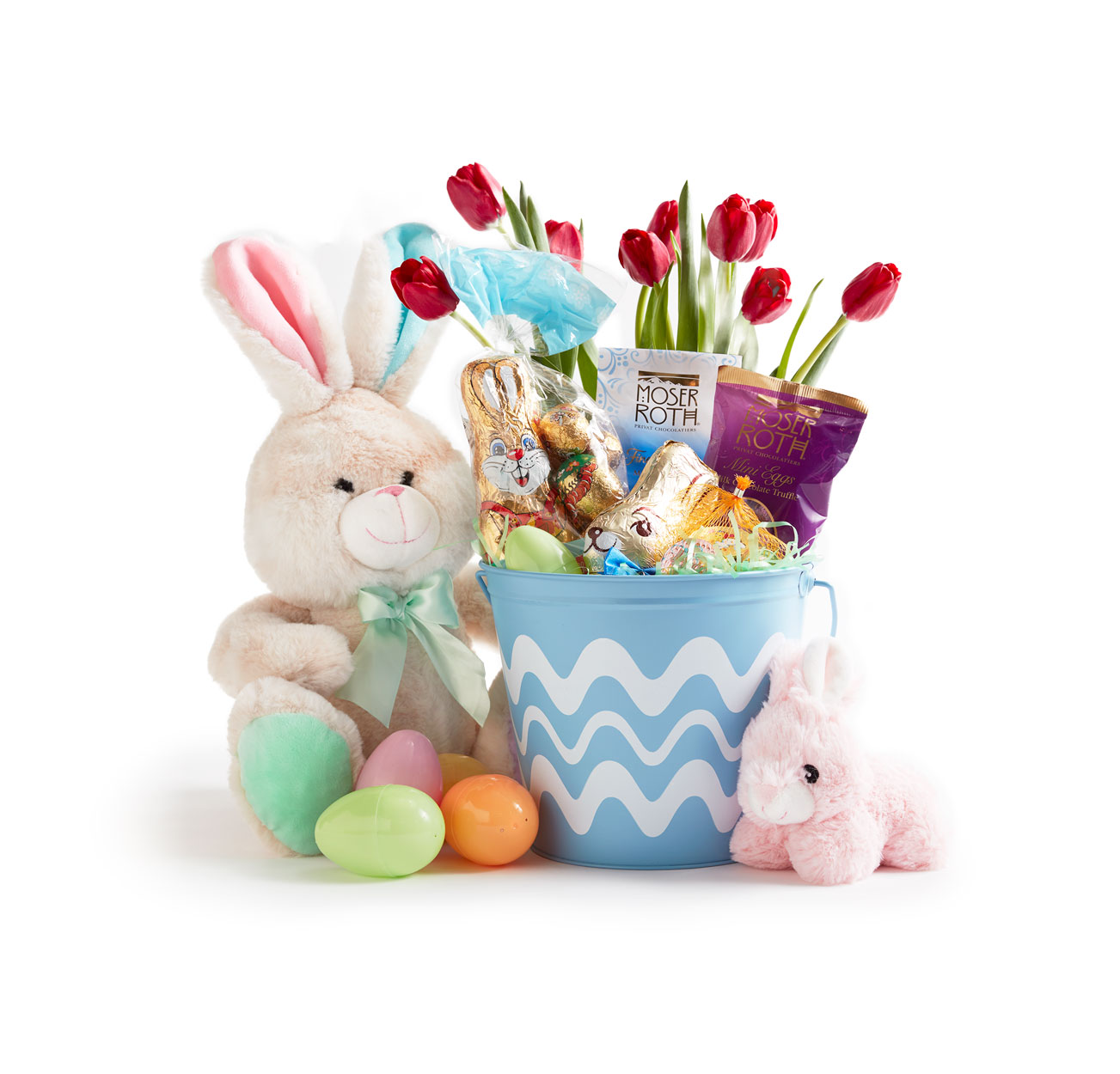 A kids Easter basket featuring chocolate, tulips and plush rabbits.