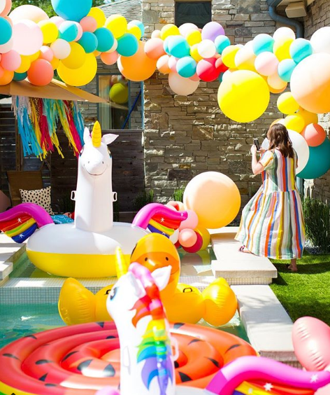 Pool party with balloons and inflatable pool toy selection.