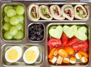 Bento box lunch with fresh fruit and turkey and cheese roll up.