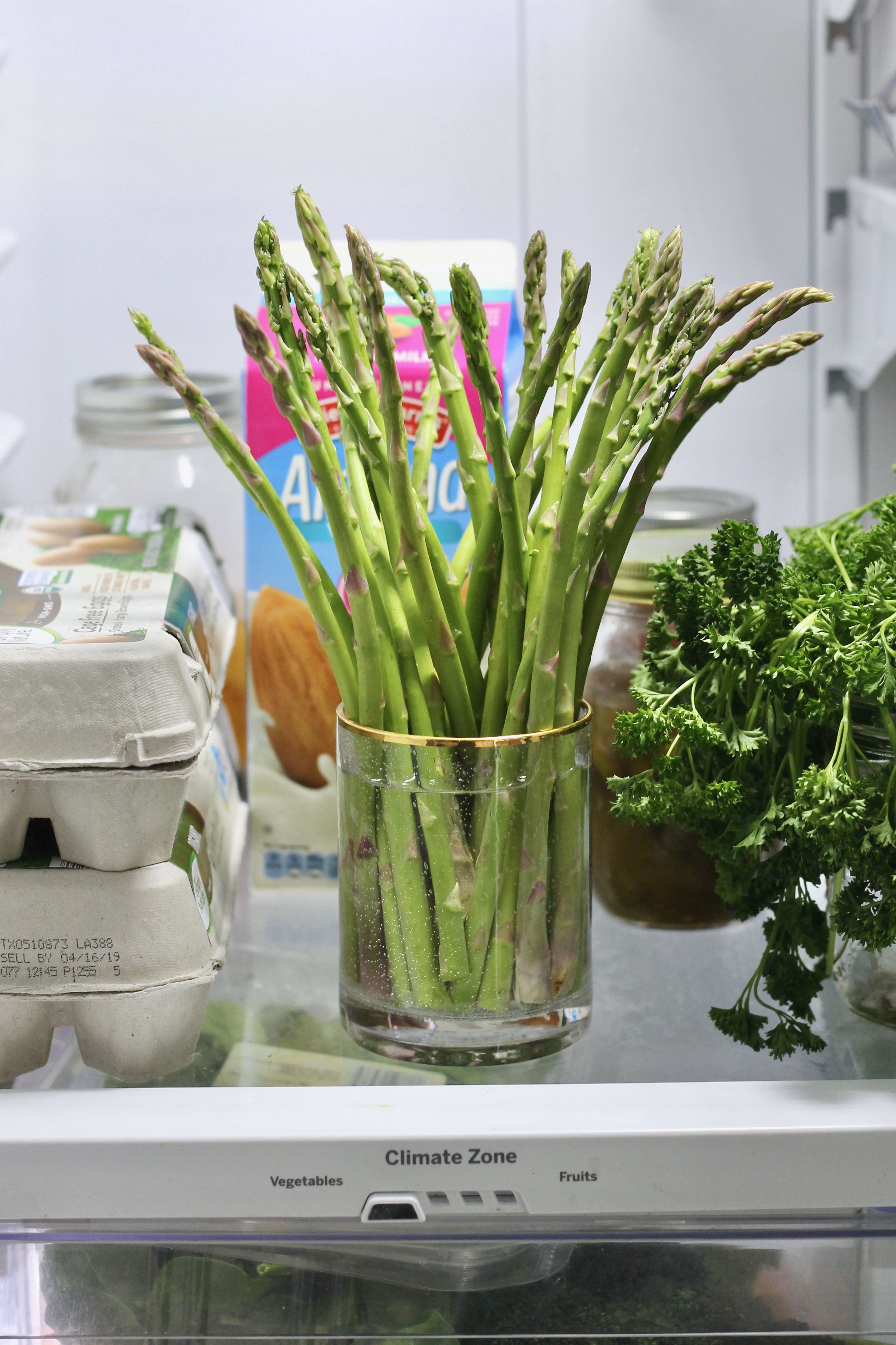 Asparagus placed upwards in a cup or water in a refrigerator